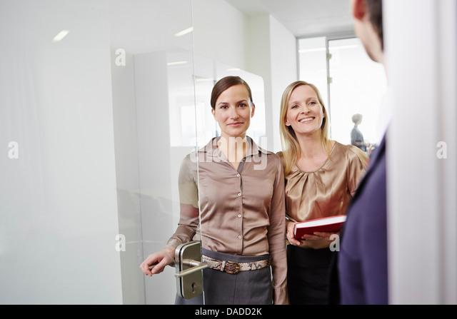 Women wearing business attire standing in door frame of office - Stock Image