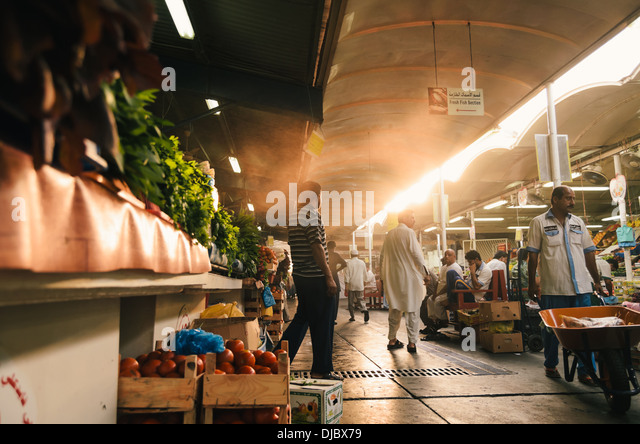 Arab men walking along one of the corridors at Deira's Fruit and Vegetable Market during sunrise. Dubai, UAE. - Stock Image