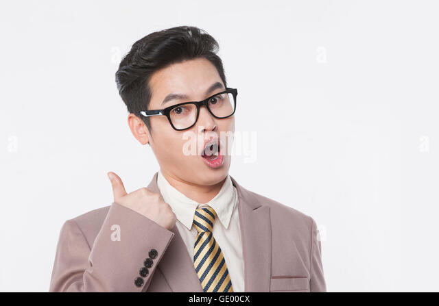 Portrait of surprised businessman showing thumb-up sign - Stock Image