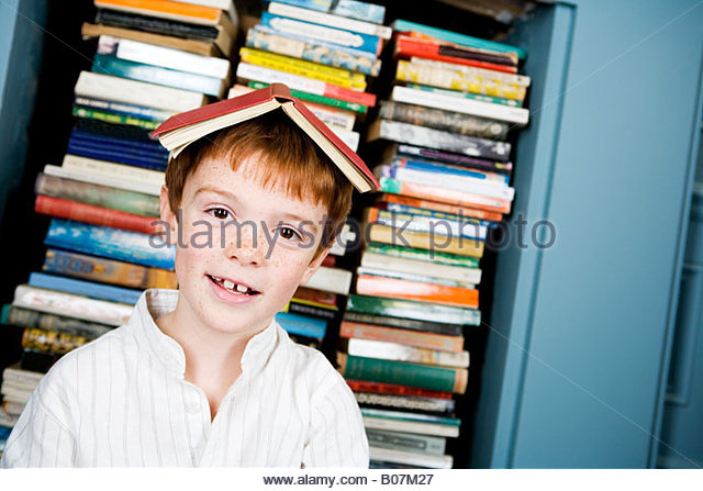 young ginger haired boy with book on his head - Stock Image