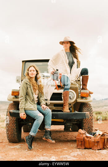 Two women sitting on the front of a jeep, on a road trip. - Stock Image