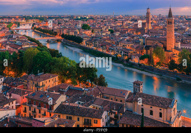 Santa Anastasia church and Torre dei Lamberti at dusk along the Adige river in Verona, Italy. - Stock Image