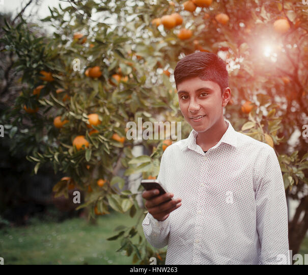 Fiji Indian boy texting on cell phone in orchard - Stock-Bilder
