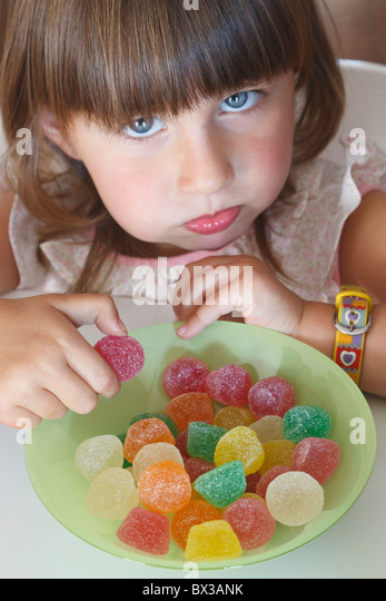 Greedy Looking Two Year Old Girl Eating From A Bowl Of Candies - Stock Image