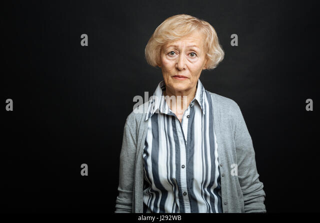 Pitiful aging woman demonstrating comparison indoors - Stock Image