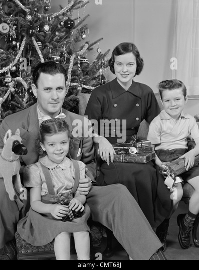 1950s FAMILY PORTRAIT BY CHRISTMAS TREE LOOKING AT CAMERA - Stock Image