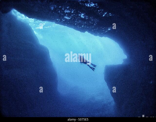 Mature male scuba diver swimming across underwater cavern - Stock Image