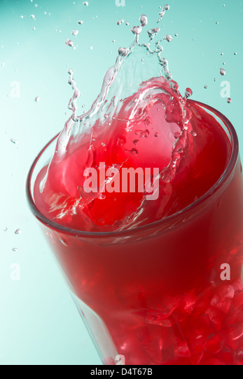 Close up of a splash on a glass of strawberry juice - Stock Image