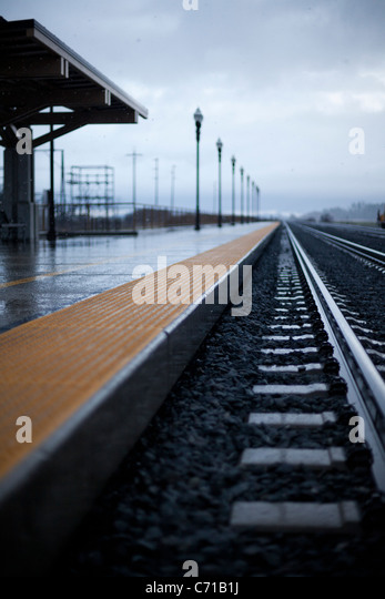 An empty train station seen through snow and winter skies. - Stock Image