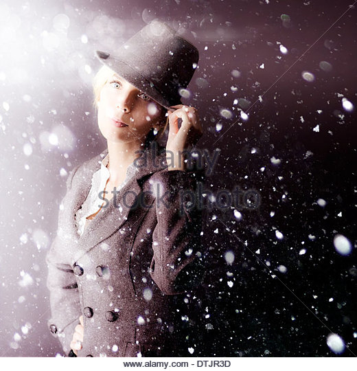 A mysterious woman operative in a hat and coat stands waiting out in a snowstorm as she watches and spies on her - Stock Image