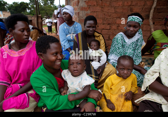 Mothers waiting to receive mosquito nets in Uganda - Stock Image