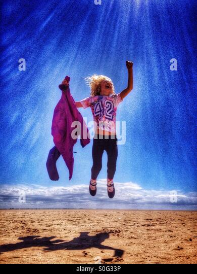 Young girl leaping for joy on the beach at Lytham St Annes - Stock Image