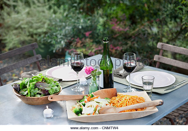 Salad and pasta on set table outdoors - Stock Image