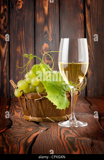 White wine with grapes on wooden background - Stock Image