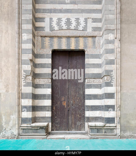 Wooden aged door surrounded by striped black and white marble decorations and stone wall at the Mosque of Sultan - Stock Image
