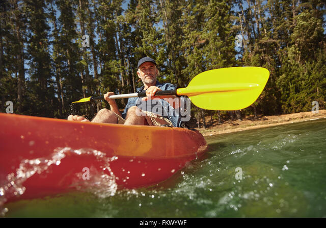 Senior caucasian man paddling a kayak in lake. Mature man canoeing on summer day. - Stock Image