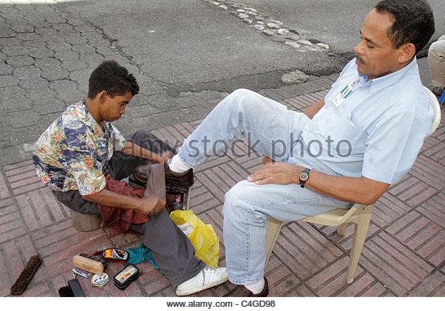 Santo Domingo Dominican Republic Ciudad Colonia Calle el Conde Peatonal Hispanic man boy teen job shoe polish shoeshine - Stock Image