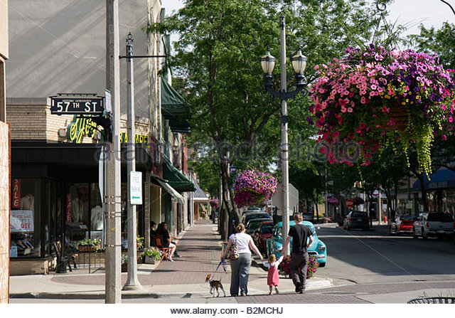 Wisconsin Kenosha Sixth 6th Avenue shopping district man woman flower planter cross street intersection girl parents - Stock Image