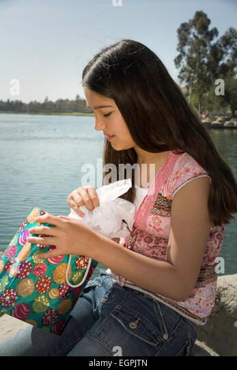 Mexican heritage. Hispanic-Caucasian girl opens gift.  MR  © Myrleen Pearson - Stock-Bilder