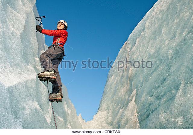 Climber scaling glacier wall - Stock Image