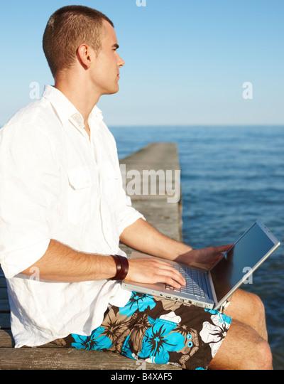 Young man using laptop on dock - Stock-Bilder