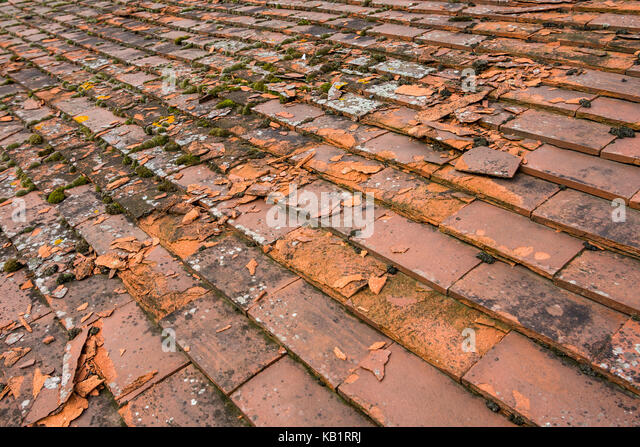 Broken roof tiles from weathering and frost - France. - Stock Image