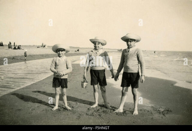 Three children dressed alike to the sea, Italy - Stock Image