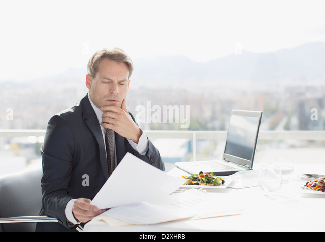 Businessman with lunch reviewing paperwork - Stock Image