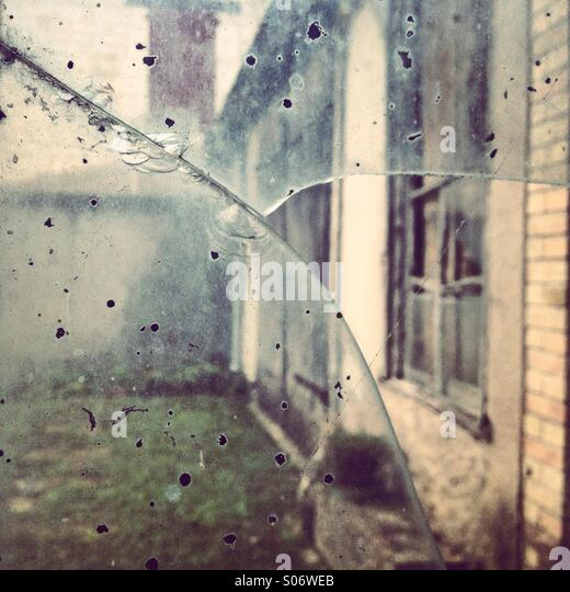 An old facade viewed through a broken glass - Stock Image