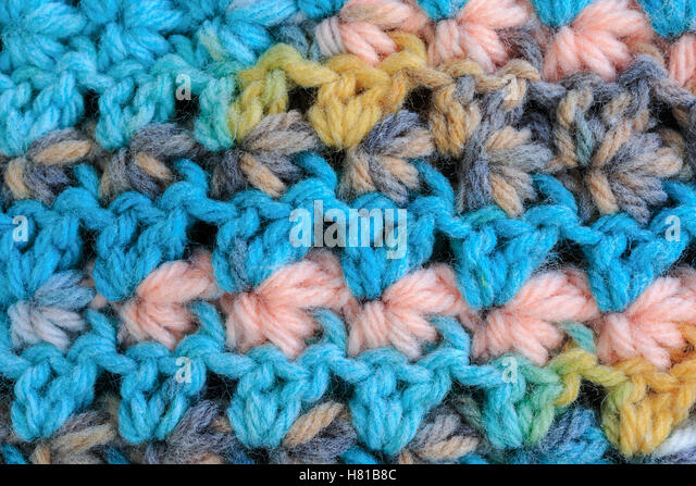 Detail of some crochet fabric showing rows of the shell stitch in a baby sweater. - Stock Image