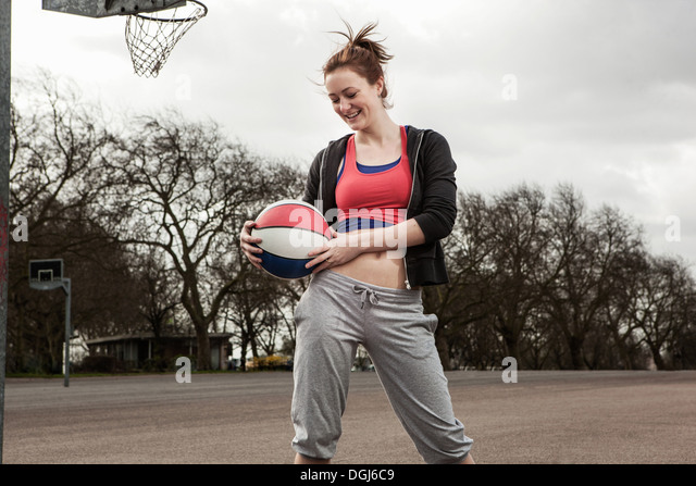 Woman holding netball to waist - Stock Image