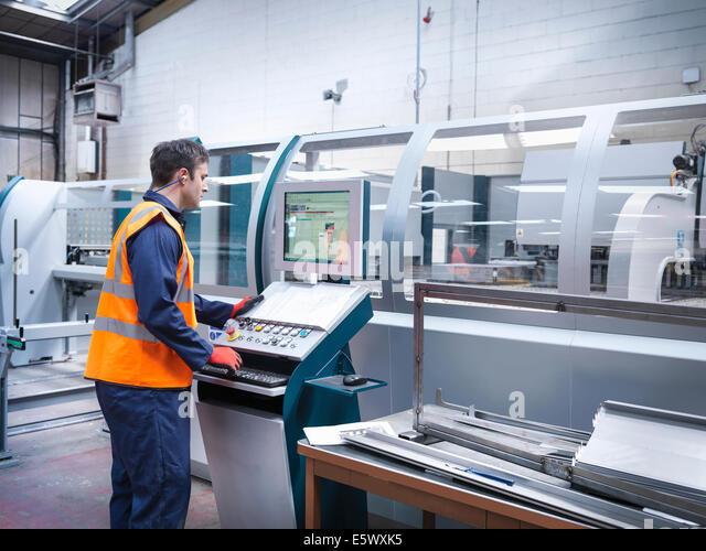 Worker using robotic metal cutting machine in sheet metal factory - Stock Image