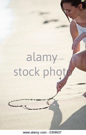 Woman Drawing Heart on Sand - Stock-Bilder