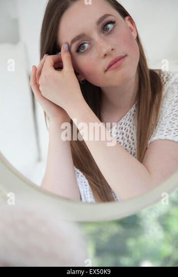 Teenage Girl Looking in Mirror Checking Eye Makeup - Stock Image
