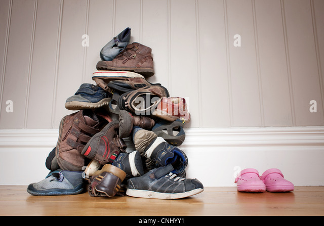 Large pile of boy's shoes beside one pair of girl's shoes - Stock Image