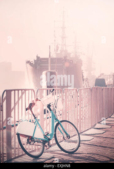 Vintage toned bicycle parked by pier with ship in a distance, sunset lens flare effect. - Stock-Bilder