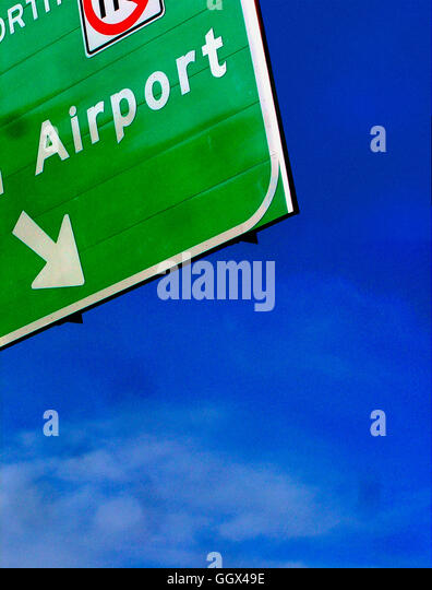 Urban Scene of Airport Sign With Directional Arrow Against a Clear Blue Sky Copy Space - Stock Image