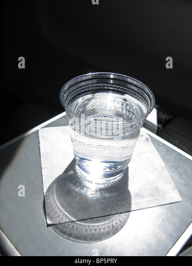 A plastic cup filled with water sitting on a white napkin on a commercial airplane's seat tray with strong window - Stock-Bilder