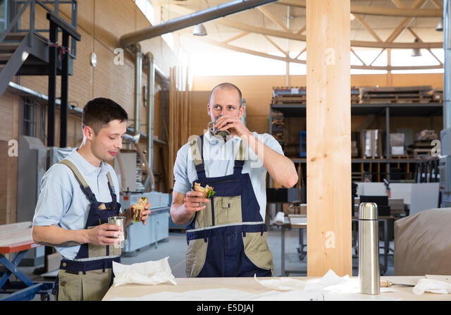 Craftsman in workshop having breakfast break - Stock-Bilder