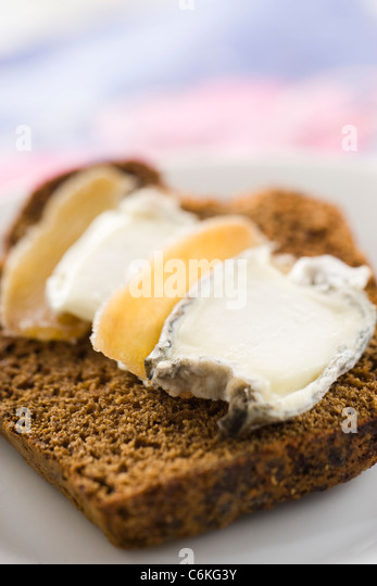Sliced gingerbread with goat cheese and candied ginger - Stock Image