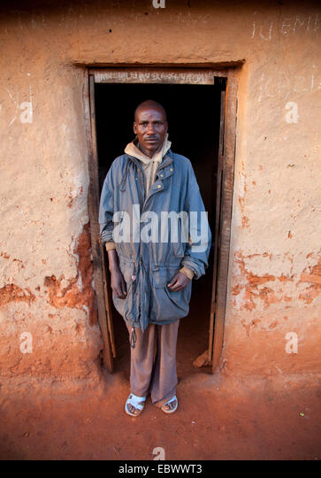 portrait of a man in front of his humble mud house in the morning light, Burundi, Near National Parc de la Ruvubu, - Stock Image