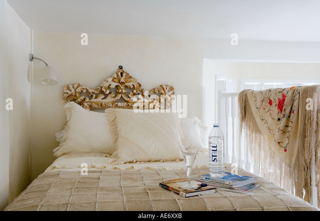 bed on mezzanine with wooden balustrade - Stock Image