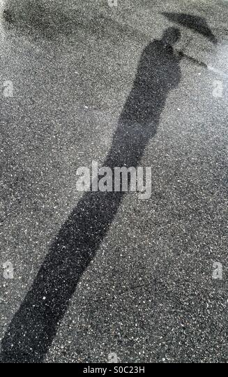 Shadow of a man with his umbrella. - Stock Image