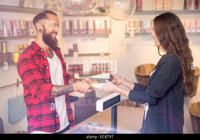 Happy owner giving candies to customer in shop - Stock Image