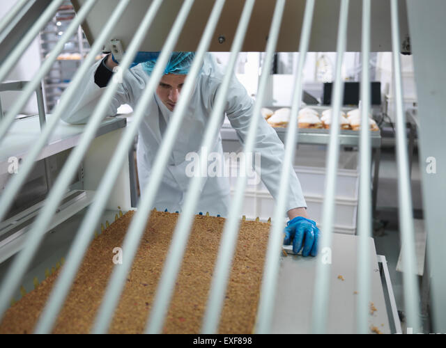 Cake product in cutting machine in cake factory - Stock Image