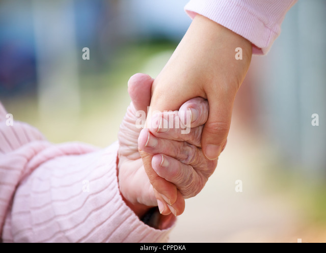 Senior Woman Holing Hands with Young Caretaker - Stock Image