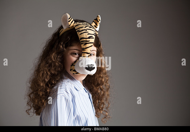 Young girl wearing tiger mask - Stock Image