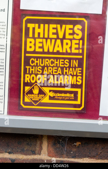 Sign warning potential thieves that the church roof is fitted with an alarm. - Stock Image