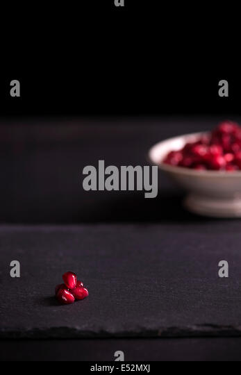 Pomegranate arils on black with more arils in an antique bowl the background. Dark moody setting. - Stock Image