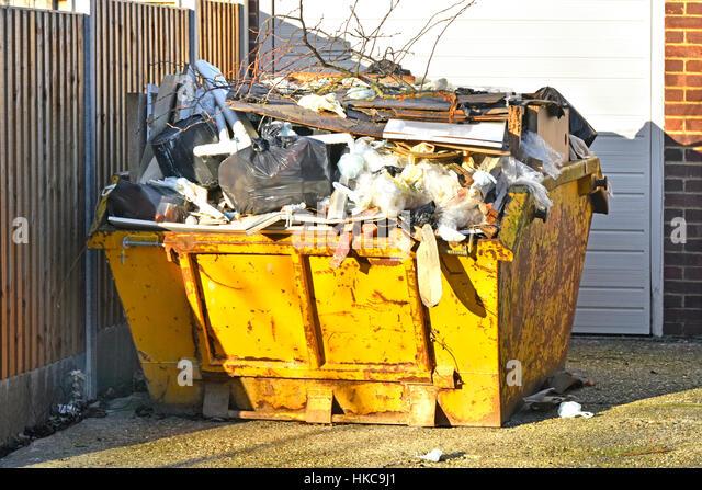 Full UK skip bin rubbish uk waste management logistics garbage trash overflowing awaiting moving to landfill from - Stock Image